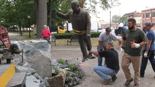 The statue of former Dearborn Mayor Orville Hubbard is dismantled in Dearborn on Tuesday, Sept. 29, 2015.