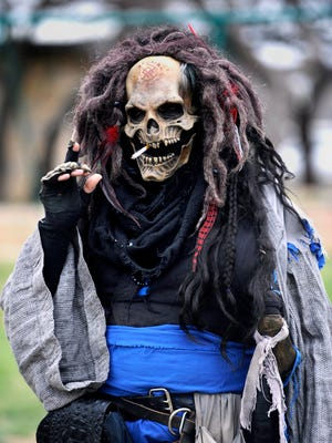 Justin Armstrong, of Midland, smokes a cigarette while wearing the costume of a character he calls Rattles on March 12 at Nelson Park. The local chapter of the live-action role-playing group Amtgard held a tournament there.