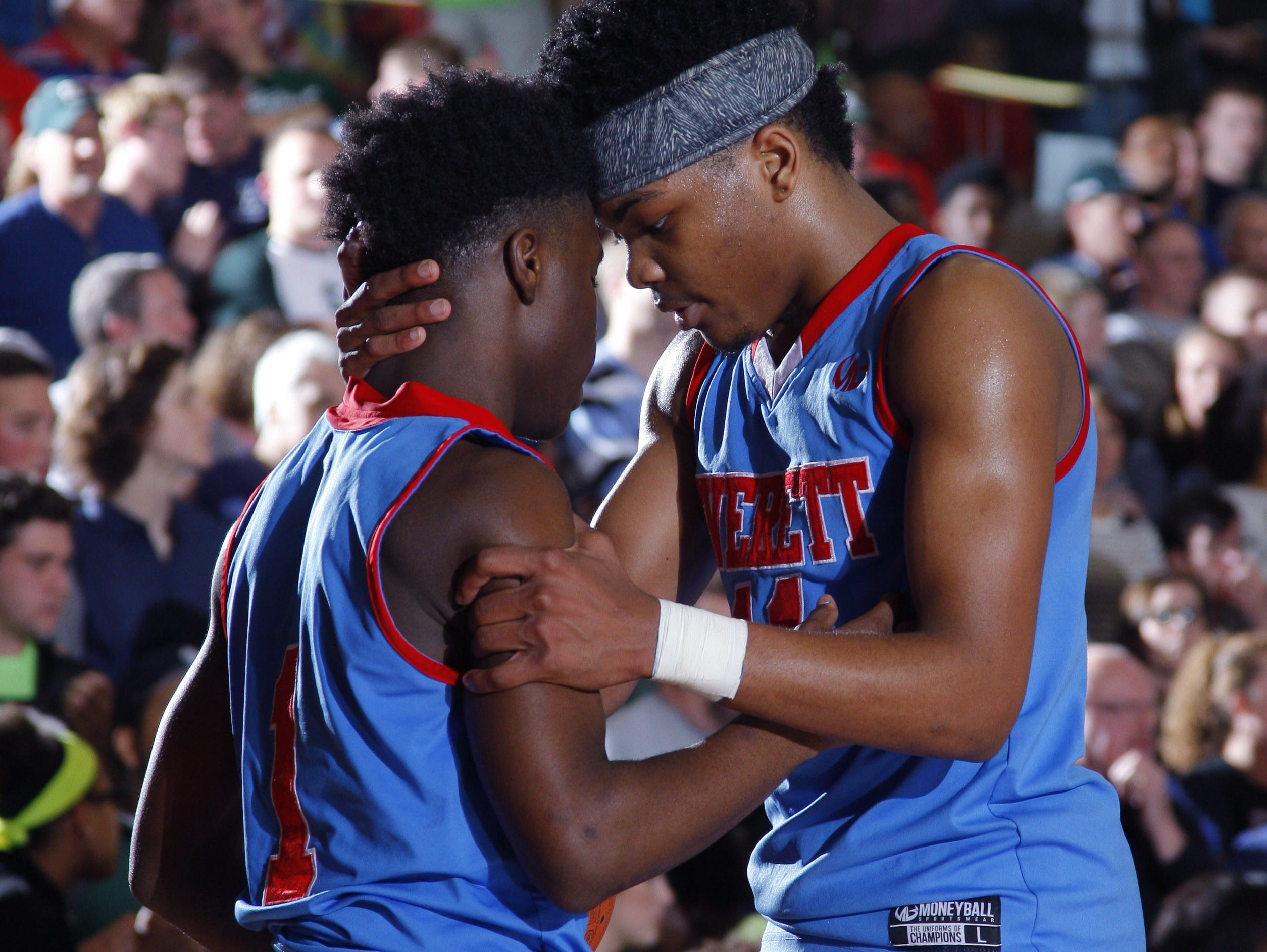 Everett's Jamyrin Jackson, right, talks with Nyreel Powell late in the fourth quarter of their regional final win over East Lansing on March 16 at Mason High School.
