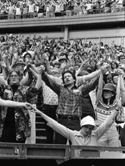 Audience members raise their arms and sing during Jesus Day celebrations at Shea Stadium in New York, June 2, 1979.