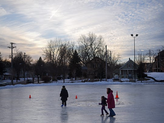 Margaret Sanger, 5, of Sioux Falls, learns to ice skate with the help of her grandma Cathy Caron, of Baltimore, as her brother, Dakota Sanger, 11, also of Sioux Falls, skates on a different part of the rink Friday, Dec. 30, 2016, on the Campus Park ice skating rink in Sioux Falls. Friday was Margaret's first time on ice skates.