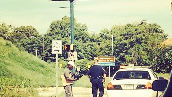 Policeman hands a homeless man boots.