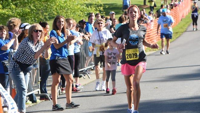 Rachel Sleeter of Hyde Park crosses the finish line to win the women's half-marathon race during the Walkway Marathon on Sunday.