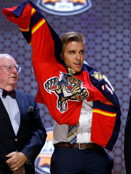 Aaron Ekblad pulls on Florida Panthers sweater after being chosen first overall during the NHL hockey draft, Friday, June 27, 2014, in Philadelphia. (AP Photo/Matt Slocum)