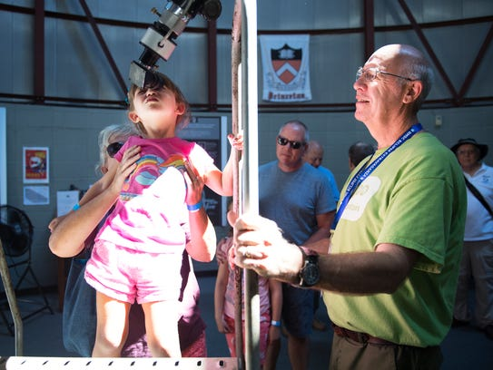 Astronomer Walter McGee watches as Leslie Hart of Greenville