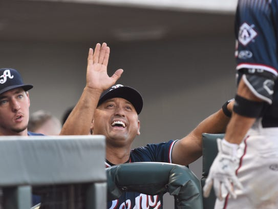 Reno Aces pitching coach Gil Heredia congratulates