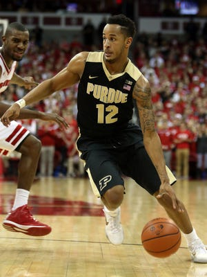 Purdue forward Vince Edwards (12) drives the ball up the court as Wisconsin forward Vitto Brown (30) follows at the Kohl Center. Purdue defeated Wisconsin 61-55.