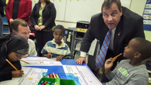 At Global Academy in Columbia Heights, Minn., New Jersey Gov. Chris Christie talks with students at the charter school while stumping for GOP governor hopeful Jeff Johnson, left, Monday, Oct. 13, 2014. (AP Photo)
