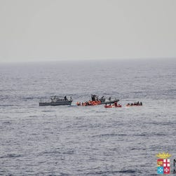 In this photo taken in the Mediterranean Sea, off the Libyan coast, Friday, May 27, 2016, rescuers help migrants to board rubber dinghies before towing them to the Italian Navy ship Vega, after the boat they were aboard sunk. The Italian navy says it has saved 135 migrants from a sinking boat and recovered 45 bodies in the Mediterranean.