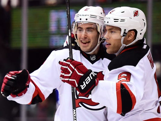 New Jersey Devils defenseman John Moore (2) celebrates his goal against the Toronto Maple Leafs with teammate Devils left wing Taylor Hall (9) during the first period of an NHL hockey game in Toronto on Thursday, March 23, 2017. (Frank Gunn/The Canadian Press via AP)