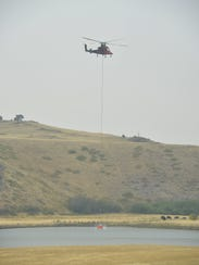 A helicopter fills its bucket in a pond on the Middle
