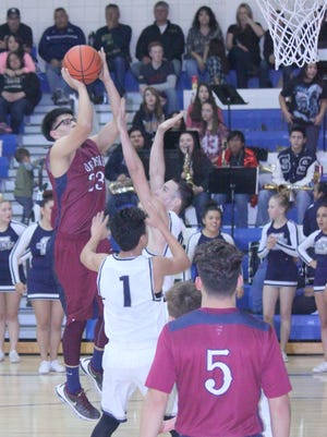 Deming's Joseph Ochoa (23) shoots over the Silver Colts defense during Tuesday's 64-60 Fighting Colts win at Silver High School in Silver City. The Colts victory capped a sweep of the home-and-away series between the two schools.