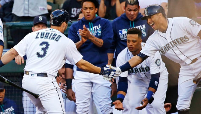 Seattle Mariners' Mike Zunino (3) is greeted at the dugout by teammates after he hit a two-run home run against the Baltimore Orioles during the second inning of a baseball game, Saturday, July 2, 2016, in Seattle. (AP Photo/Ted S. Warren)