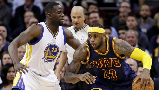 Cavaliers forward LeBron James, right, drives past Warriors forward' Draymond Green during the first quarter on Feb. 26 in Cleveland.