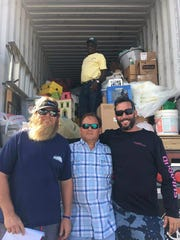 The last container: Patrick Price of Jensen Beach (left), Joe Rieger of Stuart (center), Seth Funt of Delray Beach (right) and Leonard Stuart of the Bahamas (in container) finish loading the last shipping container to depart the Stuart Jet Center in October 2016 after more than 50 tons of relief supplies were sent to West End, Bahamas over seven days following Hurricane Matthew.