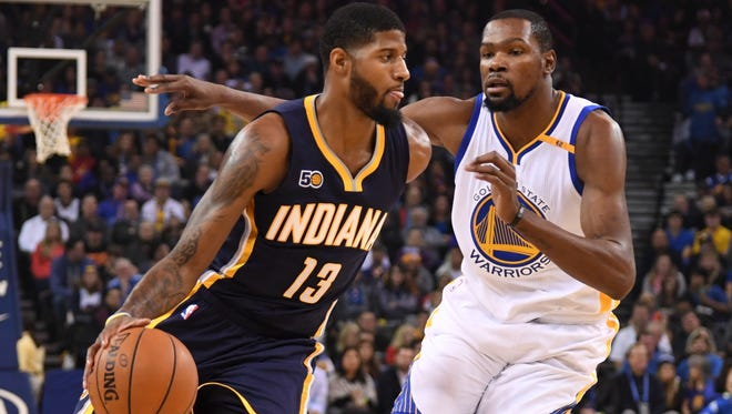 Indiana Pacers forward Paul George (13) dribbles the basketball against Golden State Warriors forward Kevin Durant (35) during the first quarter at Oracle Arena.