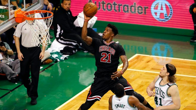 Chicago Bulls forward Jimmy Butler (21) goes to the basket past Boston Celtics guard Marcus Smart (36) and center Kelly Olynyk (41) during the third quarter in game one of the first round of the 2017 NBA Playoffs at TD Garden.