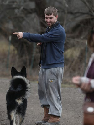 Dylan Saxon of Fairport tries to get Bear to play with the other dogs at the Dog Park at Ellison Park.