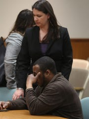 Assistant Public Defender Katie Higgins pats Silvon Simmons arm as they wait for the court room to clear for him to leave.