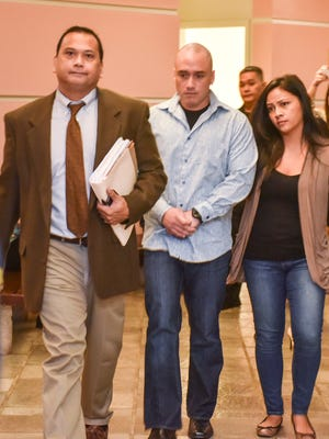 Guam Police Officer Mark Torre Jr., center, walks out of the courtroom after his arraignment hearing at the Guam Judicial Center on July 29. Torre, who faces allegations of murder, manslaughter and aggravated assault in the July 13 shooting death of fellow officer Sgt. Bert Piolo, pled not guilty to the charges during the hearing.
