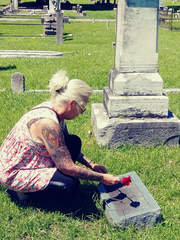 Stacey Humphreys places a rose behind the headstone