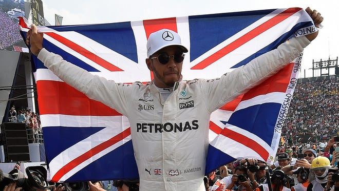 Lewis Hamilton celebrates after clinching his fourth Formula One championship after a ninth-place finish in Sunday's Mexican Grand Prix.