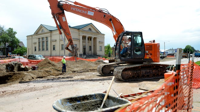 Contractors work in a hole in the ground as construction continues Tuesday on Monroe Avenue in Green Bay.