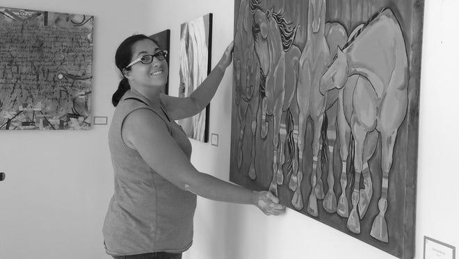 Carissa Sorensen hangs a painting in the Thrasher Annex gallery.