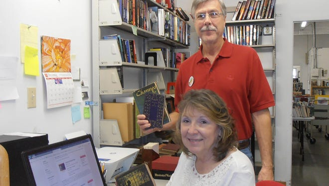 Book Depot volunteers Donna and Glenn Wells research vintage books to prepare for the sale.