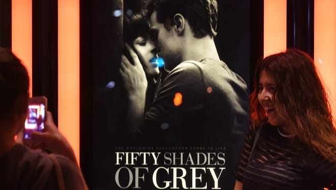 Women pose for photos in front of a poster advertising the movie 'Fifty Shades of Grey' on its opening day in Los Angeles on February 12, 2015. The long-anticipated movie version of the bestselling erotic novel began its worldwide rollout opening in theatres across France, Germany, Belgium and Serbia, days ahead of its key target territory the United States.