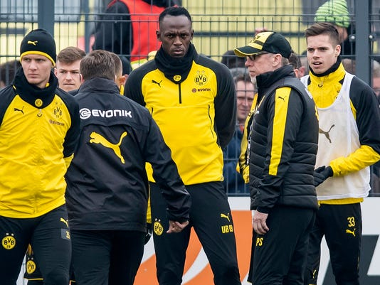 Jamaica's former sprinter Usain Bolt, third from right, takes part in a practice session of the Borussia Dortmund soccer squad in Dortmund, Germany, Friday, March 23, 2018.  Dortmund  head coach Peter Stoeger stands second right. (Guido Kirchner/dpa via AP)