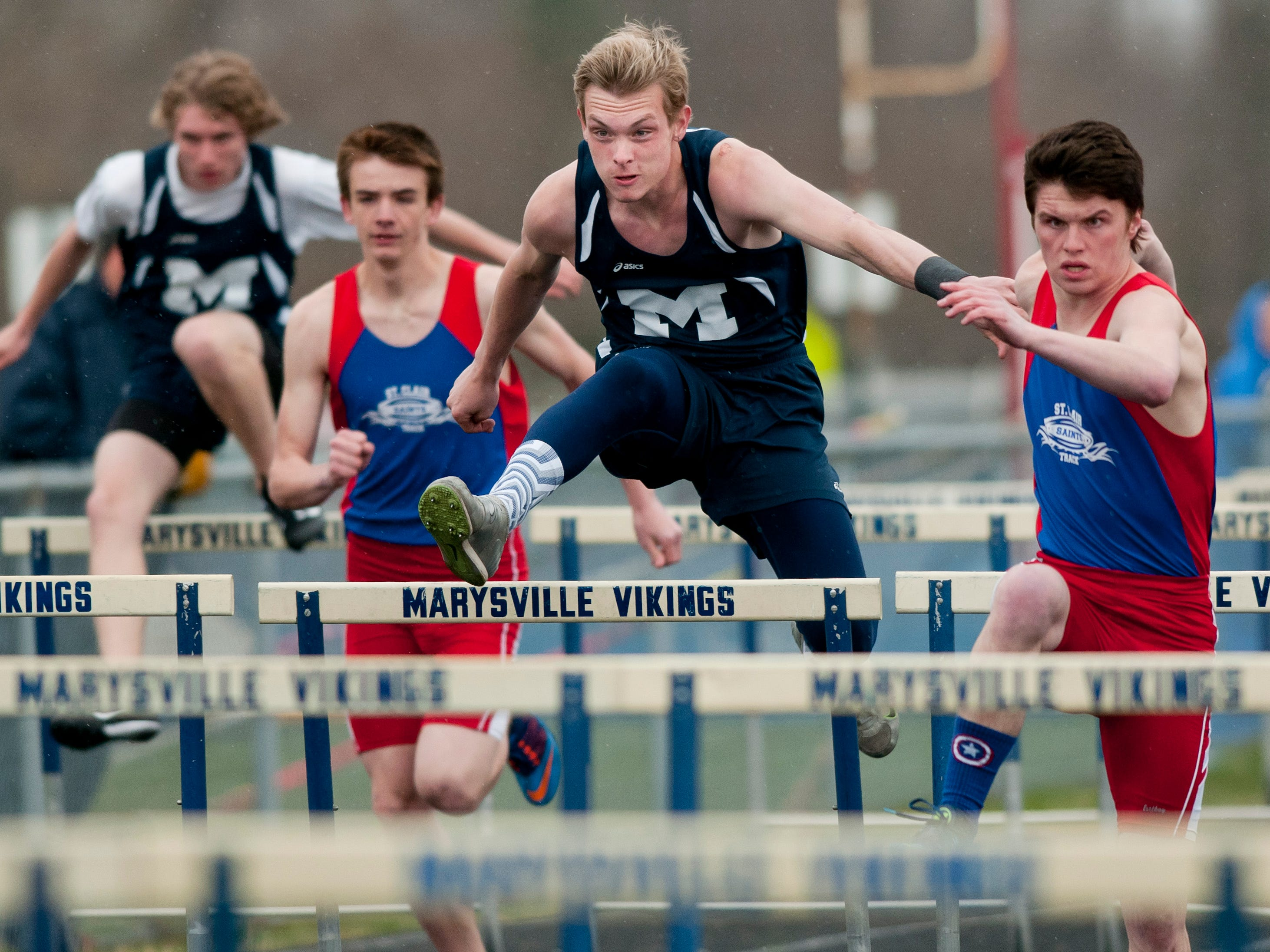 Marysville junior Mike Rasnick and St. Clair senior Nathan Roberts compete in the hurdles during a track meet Thursday, April 30, 2015 at Marysville High School.