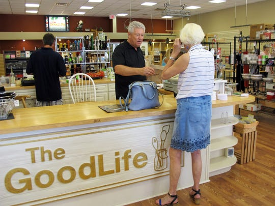 Dave Schwarz, center, waits on a customer Friday, June 8, 2018, at his store, The Good Life, in North Naples. The local family-owned kitchen gadget store is permanently closing Saturday, June 16, after operating for nearly half a century.