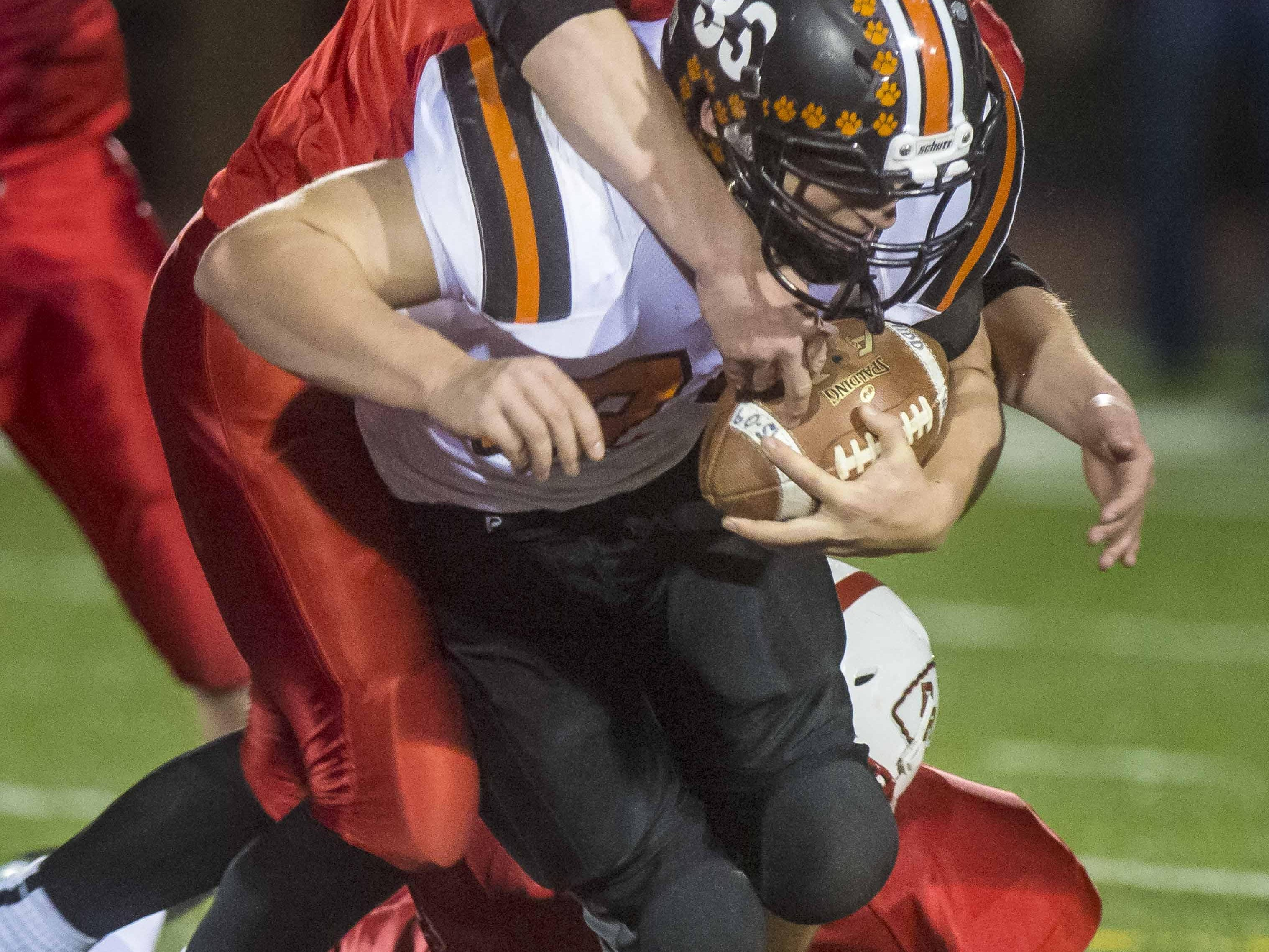 Middlebury's Cortland Fischer, center is tackled by Rutland's Jared Migliore, left, and Bailey Peters in the D1 state football championship in Rutland on Saturday, November 7, 2015.