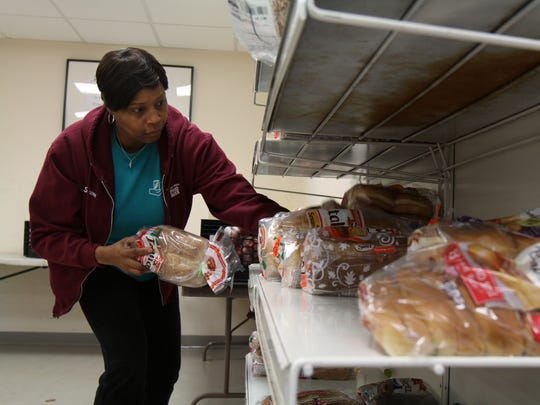 Serena Bennerman of Somerset, operations manager, straightens the bread shelf before the doors open for clients at the Franklin Township Food Bank, where volunteers help provide food to those in need.