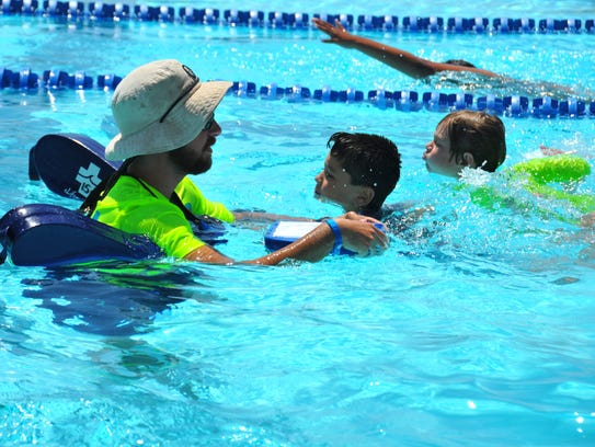 Connor McClanahan works with young swimmers. Children