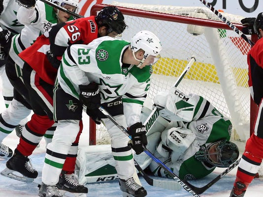 Dallas Stars goaltender Ben Bishop (30) smothers the puck to make a save as defenseman Esa Lindell (23) and Ottawa Senators left wing Magnus Paajarvi (56) look on during second-period NHL hockey in Ottawa, Friday, March 16, 2018. (Fred Chartrand/The Canadian Press via AP)