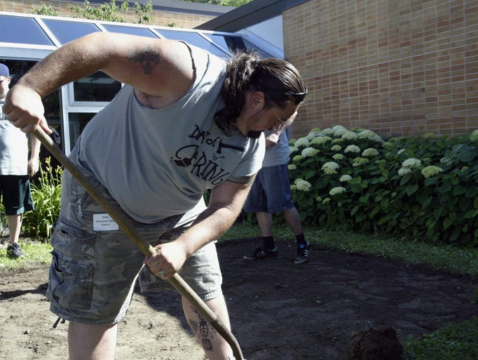 Matt Anzia, an employee of Plymouth Foam, participates in the annual Day of Caring event on Thursday, July 17 by digging a garden plot at the Sheboygan Senior Activity Center.