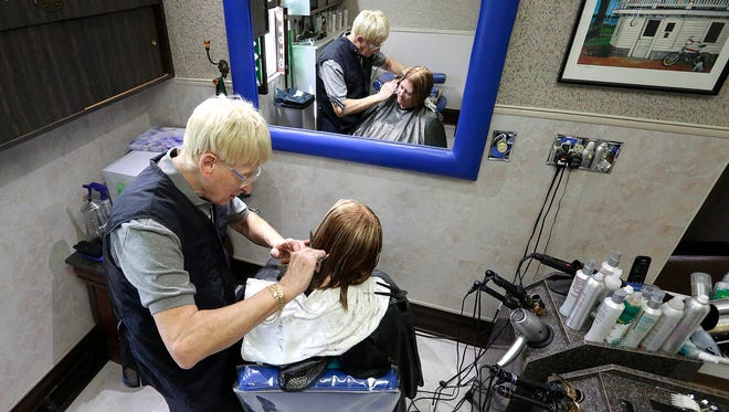 Don Abler cuts the hair of longtime client Linda Gurath of Onalaska on his last day in business in Fond du Lac Saturday. Abler cut hair for more than 50 years.