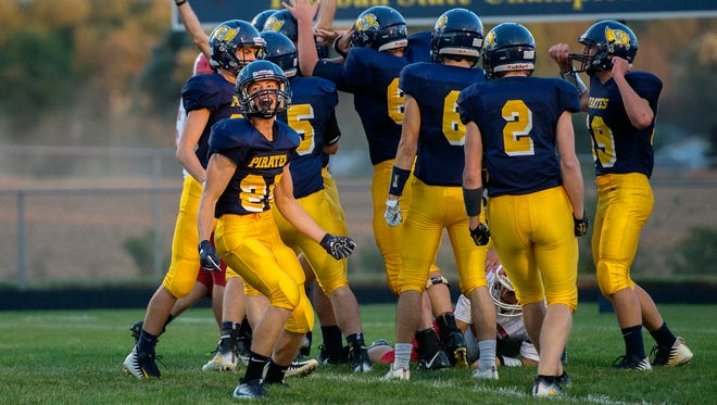 Pewamo-Westphalia's Evan Thelen, left, celebrates with his teammates after the Pirates recover a Laingsburg loose snap in the end zone during the first quarter on Friday, Sept. 29, 2017, in Westphalia.