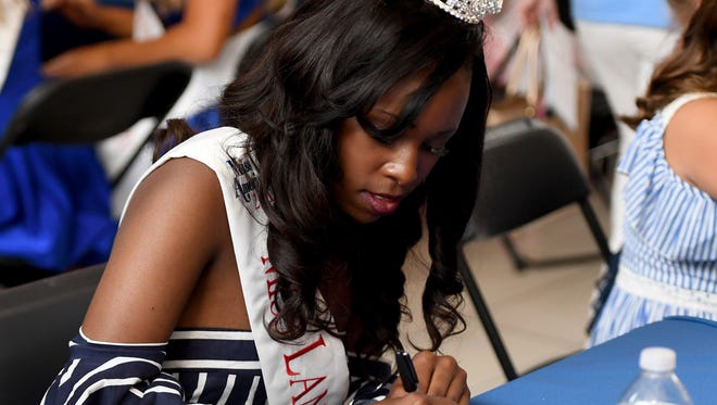 Miss Lane College DeNisha Mattox sings her name in a program book during the 2018 Miss Tennessee Scholarship Pageant Meet-and-Greet at the Old Hickory Mall, Sunday, June 17.