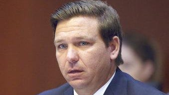 FILE - In a June 4, 2019 file photo, Florida Gov. Ron DeSantis listens to the proceedings during a Florida cabinet meeting, in Tallahassee, Fla.  Floridians could eventually gain access to cheaper prescription drugs from Canada and other foreign countries under legislation signed into law Tuesday, June 11, 2019 by Gov. Ron DeSantis, if the federal government gives it a green light.