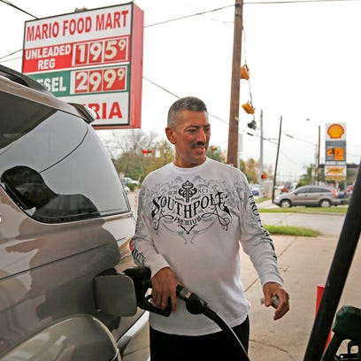 Luis Duran fills his vehicle with gasoline at the Mario Food Mart in Houston in this file photo