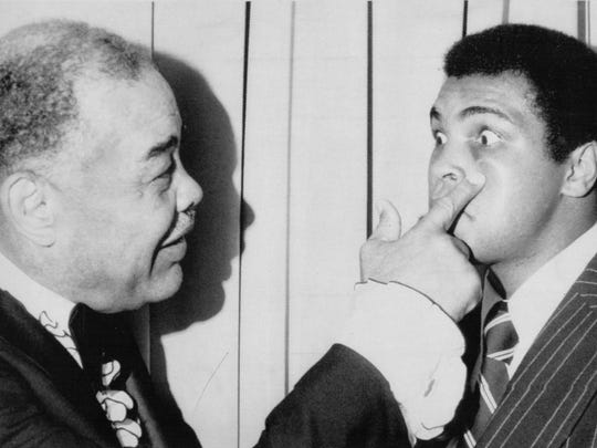 Former heavyweight champion Joe Louis, left, jabs a finger under the eye of then-heavyweight champ Muhammad Ali in New York.