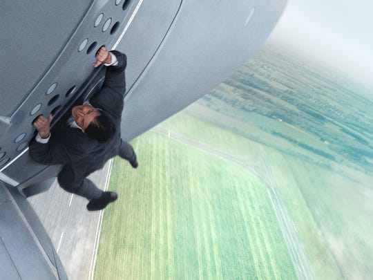 Tom Cruise hangs off a plane to get the job done for