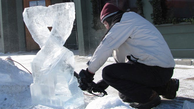 A carver works on his ice sculpture outside On Deck Clothing on North Third Avenue during a past Fire & Ice Festival in Sturgeon Bay. Carvers are being sought to take part in the competition for this year's festival.