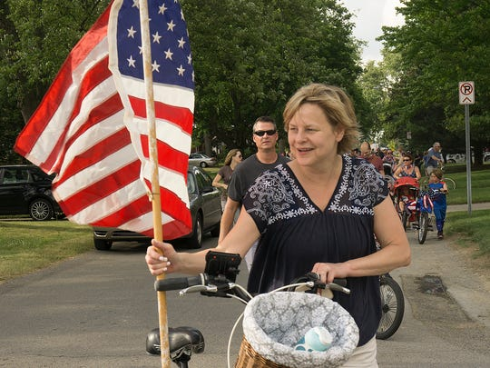 Linda Kemp carries the flag in the parade.