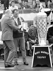 A.J. Foyt, right, winner of 1967 race, accepts trophy due him as three time winner at Indianapolis Speedway in ceremony on May 25, 1968, in Indianapolis. Presentation is by Jim Bere, left, President of Borg-Warner, which donates trophy. (AP Photo)