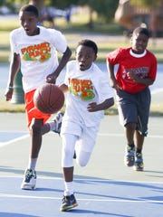Jerome Perkins, Jr., 12, leads a charge up court as boys play in the Pyramid Punch basketball league in Wilton Park.