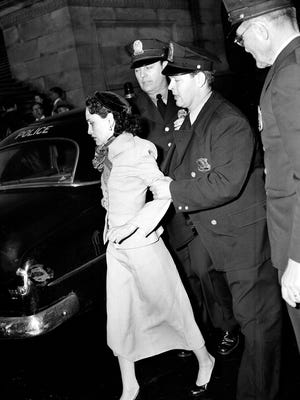 Puerto Rican nationalist Lolita Lebron is led away by police officers following her arrest after a shooting attack on Capitol Hill in Washington on March 1, 1954.